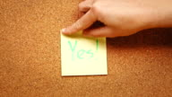 Person sticking a note reading 'Yes' on a cork board video