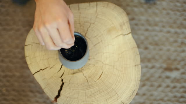 Person Stirring Drink In Cup On Tree Stump video