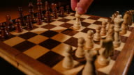 A person takes the white king and lies him down at the center of a chess board as a sign of surrendering video