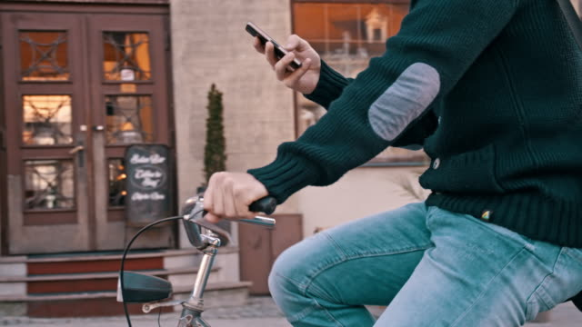 SLO MO Person typing sms on the bicycle video