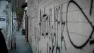 Person walking in city filled with tension and vandalism video