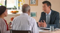 Personal banker talking to multi ethnic senior couple at home video