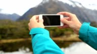 Personal perspective of a woman hiking and taking a smart phone picture of the mountain lake landscape video