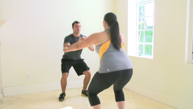 Personal Trainer Exercising With Overweight Woman video