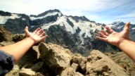 Person's arms stretches towards the Mount Cook video