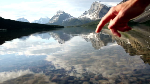Person's finger touches surface of mountain lake video