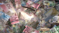 Perspective View, through Sunlight, of Canadian Money Flying By (Loop) video