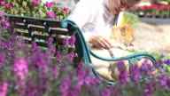 pet owner and  pomeranian dog sitting on bench in flower garden video