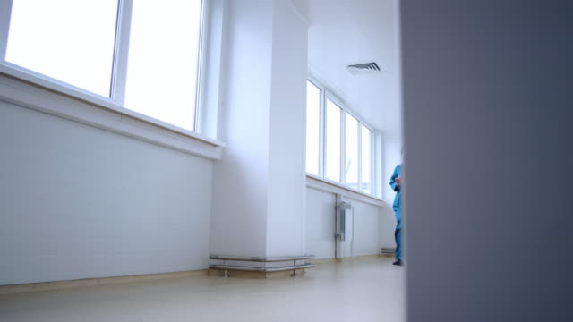 Pharmaceutical woman with tablet going in white corridor. Woman tablet computer video