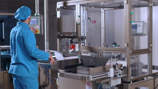 Pharmaceutical worker operate industrial equipment at pharmaceutical plant video