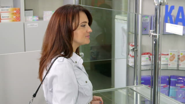Pharmacist assistant serving woman at pharmacy video