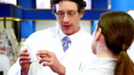Pharmacist assisting the bottle of drug to customer video