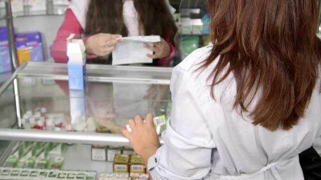 Pharmacist giving health advice to the buyer in pharmacy video