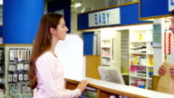Pharmacist giving medicine package to customer video