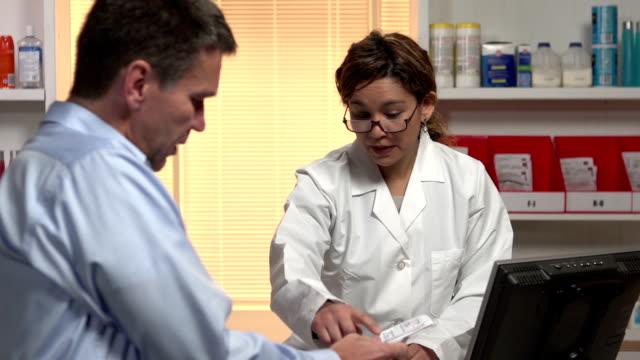 Pharmacist giving the patient prescription drugs video