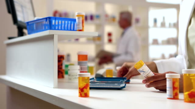 Pharmacist hands fill Prescription Bottles video