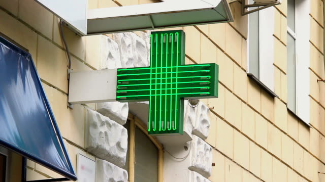 Pharmacy, drug store green neon cross lighted at daytime, city video