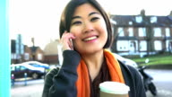 Phone chat, holding a coffee in a British street. video