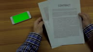 phone devices Screen Mock Up and man hands holding  a standard form of business contract with text video