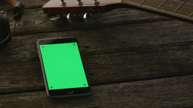 Phone with Green Screen in Portrait Mode Laying on Wooden Table next to Guitar and Headphones. Causal Lifestyle video