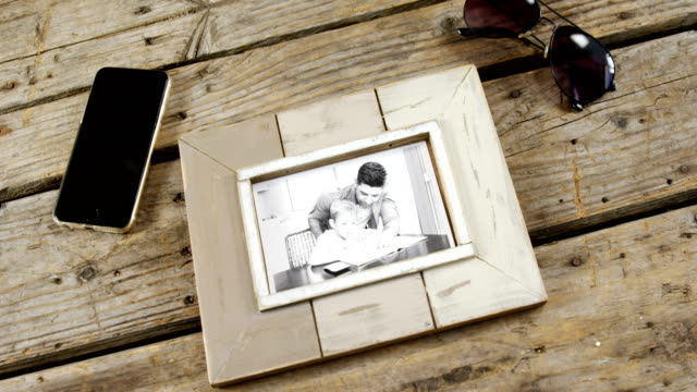 Photo frame, sunglasses and mobile phone on wooden plank video
