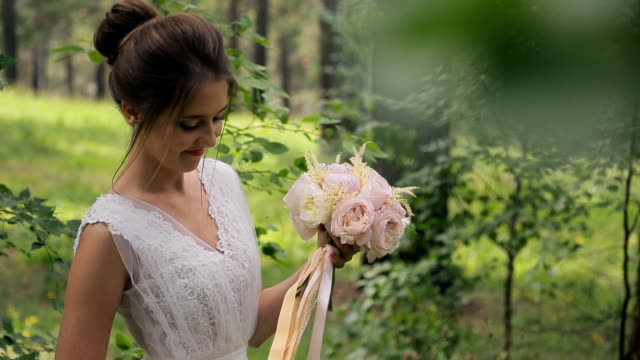 Photo shoot of bride in wedding dress sniffing flowers in forest video