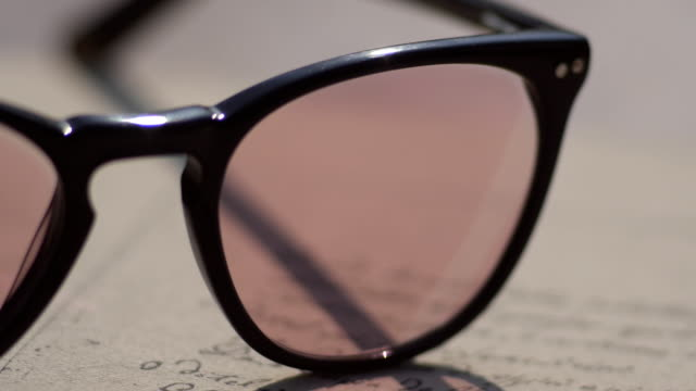 Photochromic eyeglasses on a book change color pink video