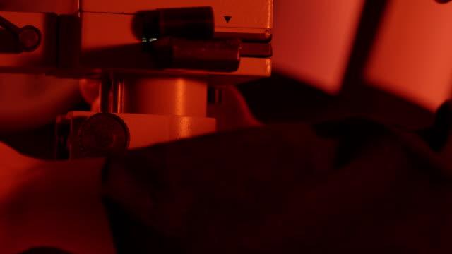Photographer adjusting the enlarger in red darkroom video