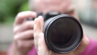 photographer frames the camera with a big lens of the camera video