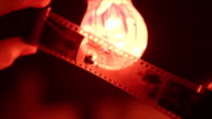 Photographer inspects negatives against red lamp in darkroom close-up video