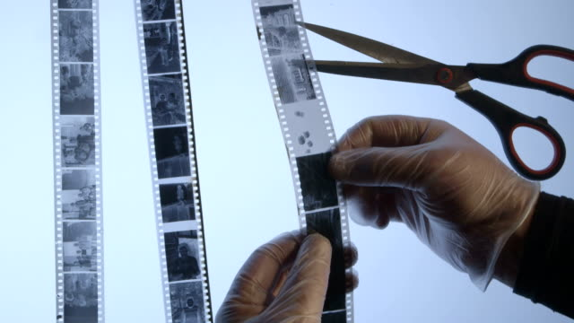 Photographer inspects strips of 35mm black and white film negatives in dark room video