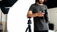 Photographer looking at photos on digital camera video