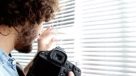 Photographer looking through window blinds video