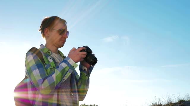 Photographer on blue sky background camera settings video