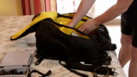 Photographer packing photo camera backpack on bed in hotel room video