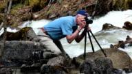 Photographer setting camera on Alaskan flooded river Skagway HD video