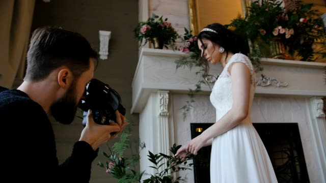 photographer shooting bride with a fireplace on the background video