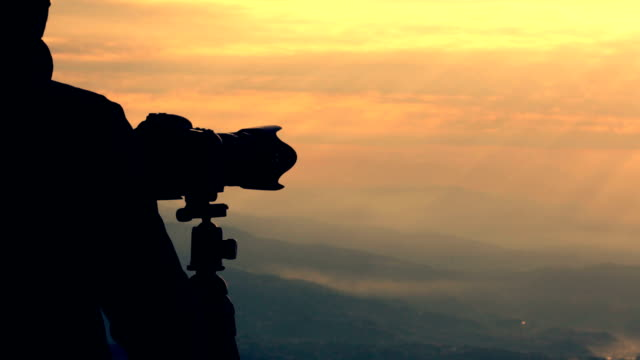 Photographer silhouette shooting on mountain top at sunrise video HD video