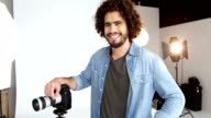 Photographer standing with digital camera in studio video