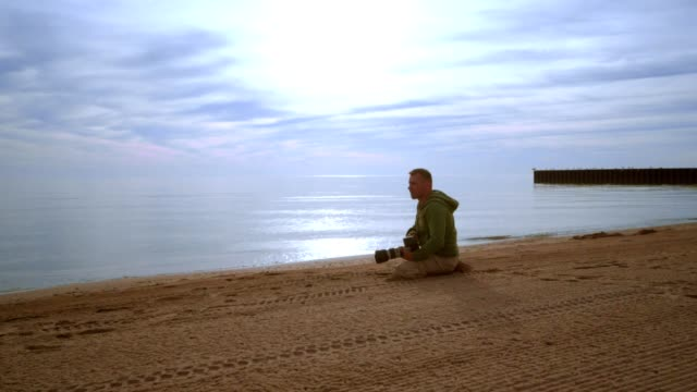 Photographer taking photo on sea beach at sunset. Photographer beach video
