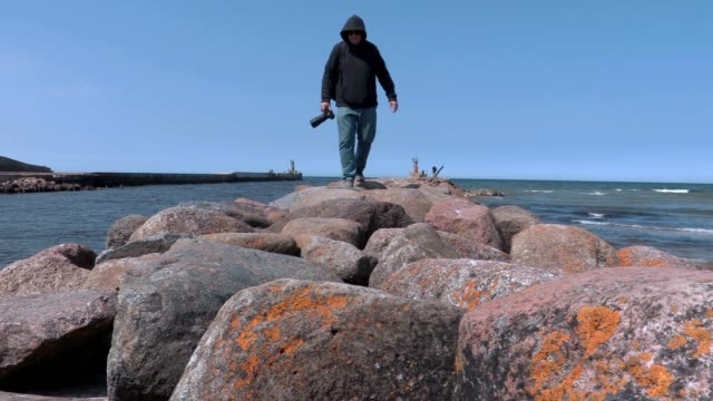 Photographer traveler walking alone on the stone pier by the sea video