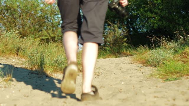 Photographer walks along dunes, in hands of camera video