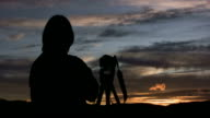Photographer with camera on tripod waiting at sunset video