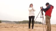 photographer woman backstage girl man photographs the outside autumn nature cold video