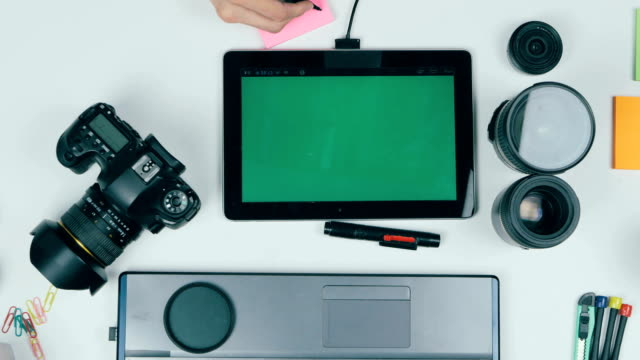Photographer working with camera and laptop at his desk. View from above video
