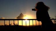 photographing the sunset: young woman climbing on the railing video