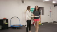 Physical therapist doing rehab with adult female patient in clinic video