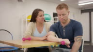 Physical therapist doing rehab with adult male in clinic video
