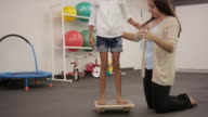 Physical therapist doing rehab with child patient in clinic video