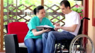 Physical therapist explaining exercises to young man in wheelchair video